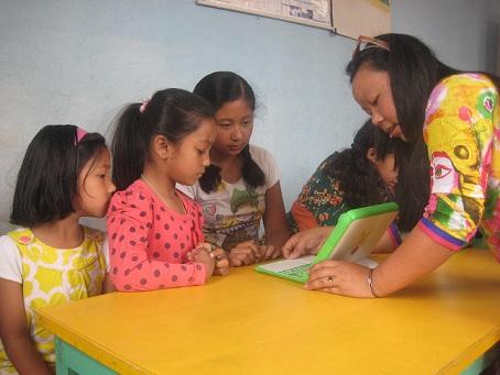 Vounteer sabita helping little girls with the laptop
