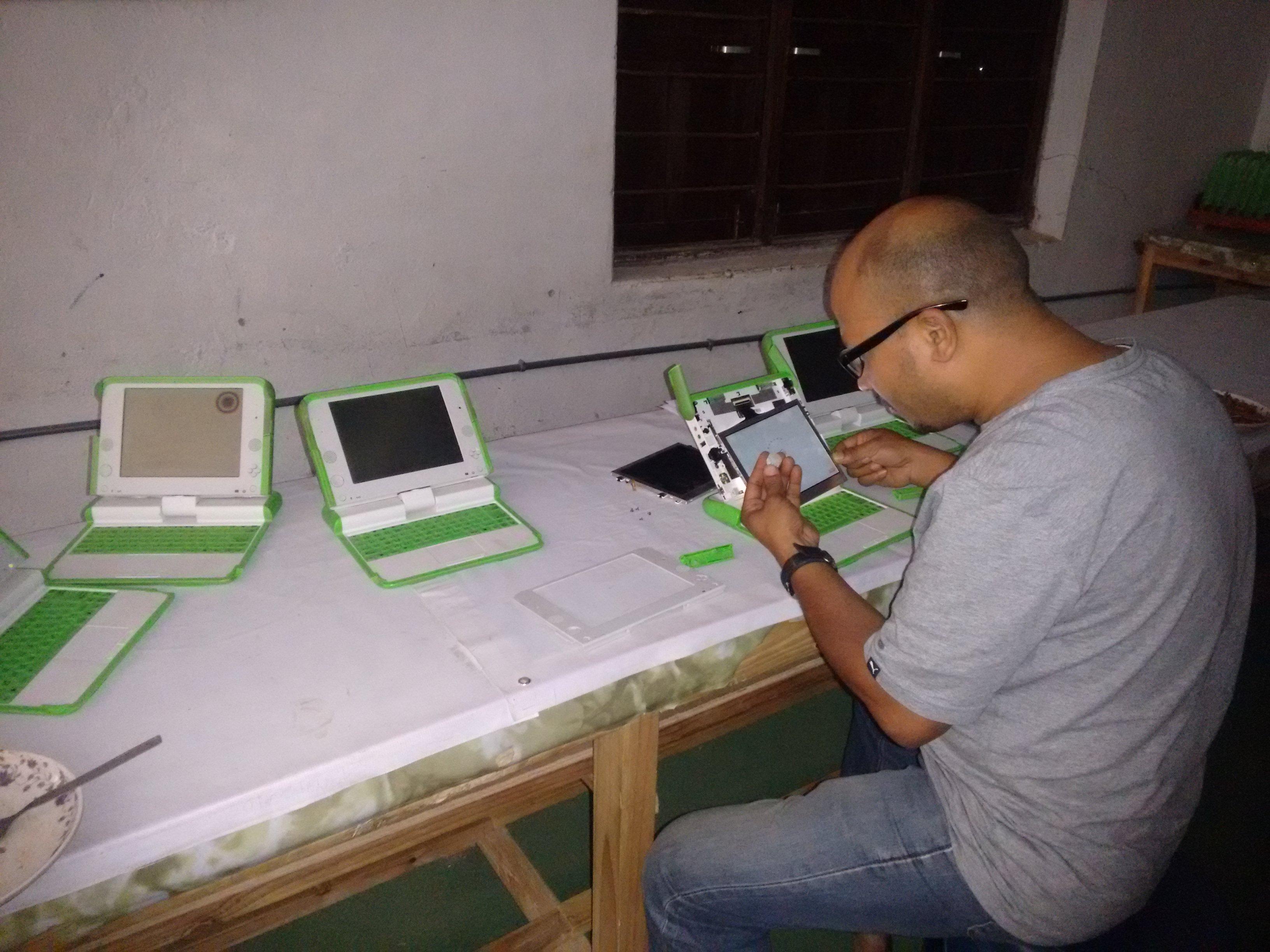 OLE Nepal's technical team member repairing damaged laptop screens in Mahendra Higher Secondary School in Baglung.